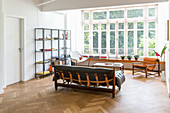 Leather sofa, chairs, shelving, and long shelf below large window in open-plan interior