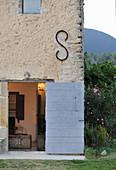 Offene Tür zum alten Steinhaus mit mediterranen Pflanzen
