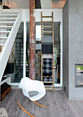 Modern rocking chair next to staircase leading to upper level