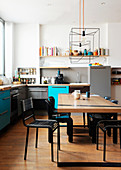 Oak table and black chairs in open-plan kitchen of loft apartment
