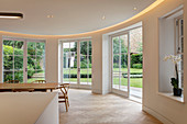 Dining area with curved wall and garden access