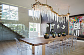 Curved chandelier with crystal icicles above table with Ghost chairs in bright, luxurious foyer