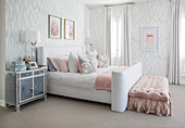 White-and-grey bedroom with pink accents and button-tufted bed bench