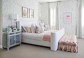 Schlafzimmer in Weiss-Grau mit rosa Farbakzent durch gepolsterte Bettbank
