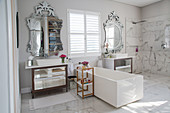 White, rectangular bathtub between twin washstands with opulent mirrors in elegant, luxurious bathroom