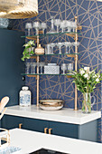 Vintage-style glasses on bar shelves against blue-and-gold patterned wall