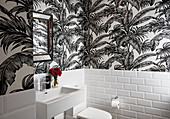Leaf-patterned wallpaper and white wall tiles in guest toilet