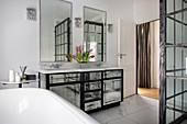 Mirrored washstand, wall- mounted mirrors, bathtub and shower cubicle in bathroom