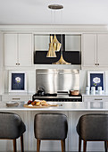 Bar stools at island counter with marble top in elegant kitchen