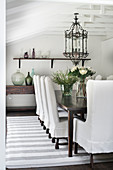 Loose-covered chairs, vintage lantern light fitting above dining table and antique console table in dining room