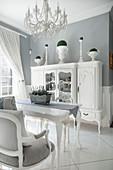 Antik Geschirrschrank in Weiß und Esstisch unter Kronleuchter in elegantem Esszimmer