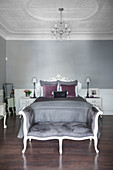 Double bed and bedroom bench in elegant bedroom with stucco ceiling