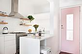 weiße Einbauküche mit Frühstückstheke neben rosa Eingangstür