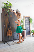 Woman next to vintage metal lockers, houseplants and chalkboard in living room