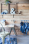Desk against wooden wall and denim clothing hung from hooks on wall