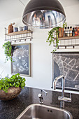 Granite kitchen worksurface with integrated sink, potted herbs and chalkboard on wall