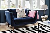Comfortable blue armchair below window