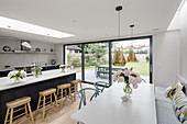 White dining table, fitted bench and open-plan kitchen with island counter and terrace doors