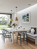 White dining table, classic chairs and fitted bench next to terrace doors