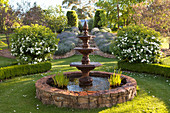 Three-tier, classic fountain in a landscaped garden
