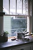 Kochtöpfe auf Küchentheke vor dem Fenster
