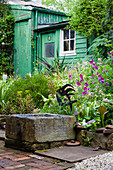 Stone trough as a pond in the garden with a weathered green wooden hut