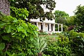 Blick durch üppiges Grün des Gartens auf ein Haus mit Veranda