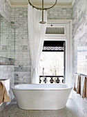 Freestanding bathtub in the bathroom with small marble tiles