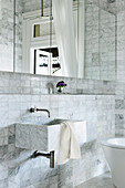 Marble sink in the bathroom with mirror cabinet and marble tiles