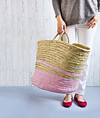 A woman holding a basket with pink stripes