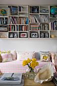 Regale mit vielen Fächern an der Wand über dem romantischen Sofa