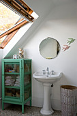 Vintage-style pedestal sink and green glass-fronted cabinet under sloping ceiling