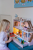 Blonde little girl playing with dolls' house with lights in interior