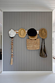 Summer hats and bags on coat rack on grey board wall