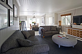 Grey sofas and round wicker table in Hamptons-style living room