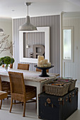 Old trunks at end of shabby-chic dining table with wicker chairs in front of board wall