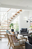 Rattan sofa and armchair in bright living room with staircase in background