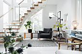 Armchair and side tables next to window and below staircase in bright living room