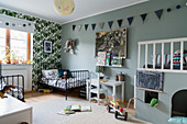 Twin beds, raised platform and grey-blue walls in siblings' bedroom