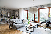Sofa, coffee table and armchair in spacious living room with glass wall, wallpaper and parquet floor