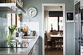 Kitchen with pale grey wall and view into dining room