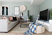 Sofa, Couchtisch, Sitzpouf, Lowboard und Fernseher im Wohnzimmer mit mintgrünen Wänden
