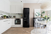 L-shaped kitchen counter, black fridge and dining area with designer chairs in bright kitchen