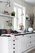 White kitchen counter with dark worksurface below window