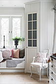 Window seat with scatter cushions next to pantry door in white kitchen-dining room