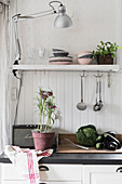Lamp clamped on shelf above kitchen counter