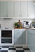 Bright fitted kitchen with white wall tiles and black-and-white chequered linoleum floor