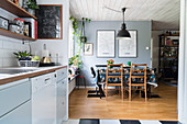 Open-plan kitchen with dining area on parquet floor and grey wall in background