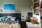 Double bed with black headboard against green-painted wooden wall