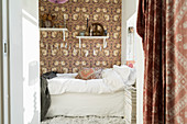 Bed with white bed linen in bedroom with wallpaper in shades of brown